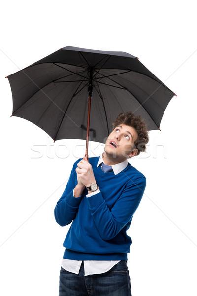Handsome businessman standing under umbrella over white background Stock photo © deandrobot