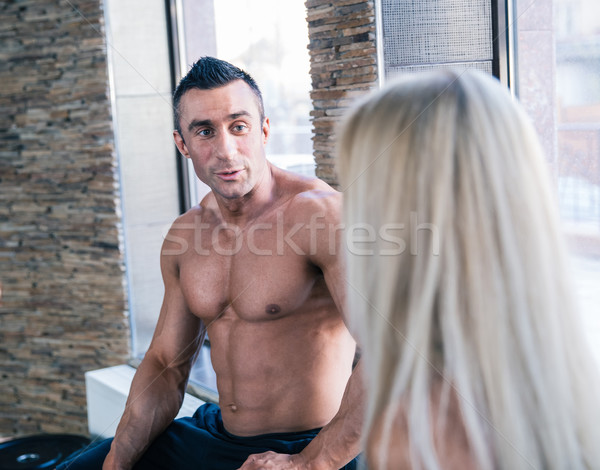 Muscular man and woman resting and talking at gym Stock photo © deandrobot