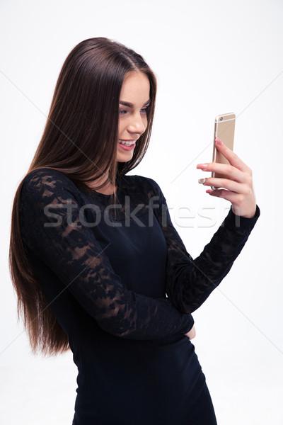Nő fekete ruha okostelefon mosolyog fiatal nő izolált Stock fotó © deandrobot