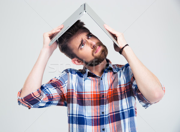 man holding laptop on his head like roof of house Stock photo © deandrobot