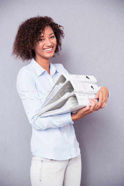 Afro american woman standing with folders Stock photo © deandrobot