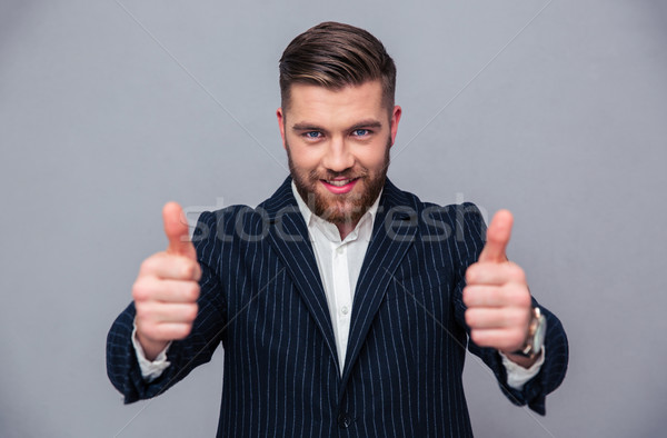 Stock photo: Portrait of a smiling businessman showing thumbs up