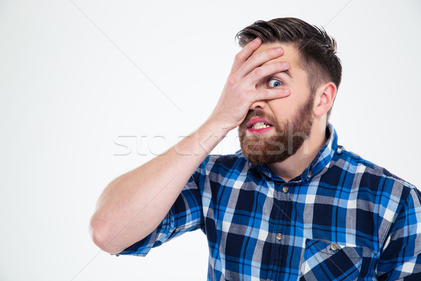 Man covering his face with palm and looking at camera through fingers Stock photo © deandrobot