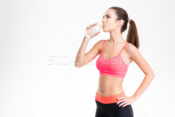 Beautiful young fitness woman drinking water from plastic bottle Stock photo © deandrobot