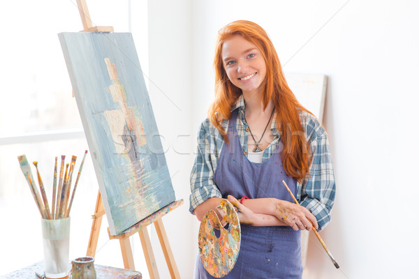 Happy satisfied woman painter finished painting picture in art studio Stock photo © deandrobot