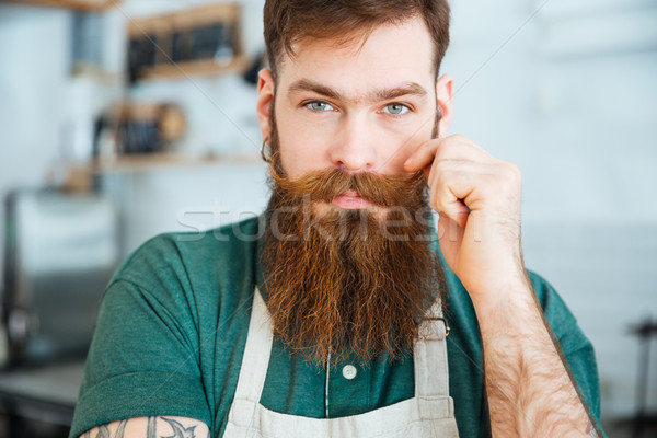 Handsome man with beard in white apron touching his moustache Stock photo © deandrobot