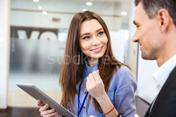 Business woman talking to her client and using tablet Stock photo © deandrobot