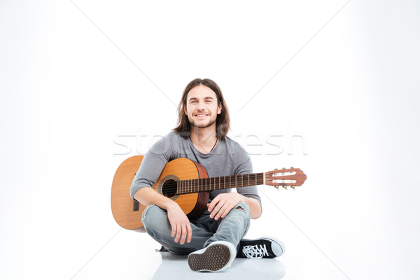 Happy handsome young man sitting on the floor with guitar Stock photo © deandrobot