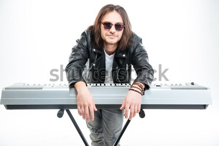 Confident young keyboardist in sunglasses standing and playing on synthesizer Stock photo © deandrobot