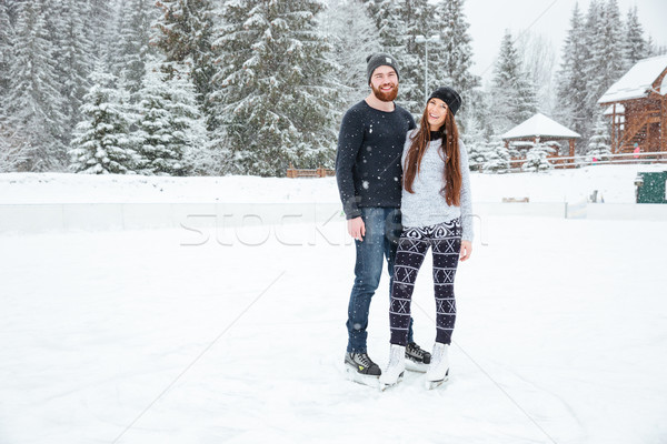 Couple in ice skates hugging and looking at camera outdoors  Stock photo © deandrobot