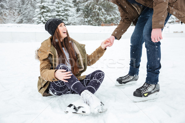 Man helping girl to stand on the ice rink Stock photo © deandrobot
