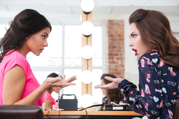 Two pretty young women sitting and arguing  Stock photo © deandrobot