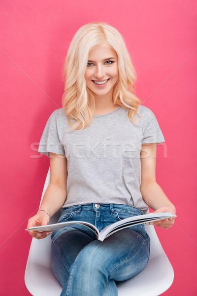 Femme souriante lecture magazine rose regarder caméra Photo stock © deandrobot