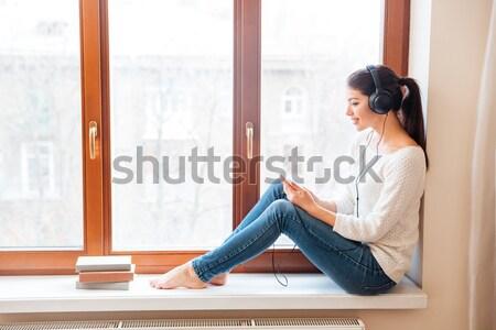 Mutlu kadın oturma pencere eşiği kulaklık bakıyor Stok fotoğraf © deandrobot