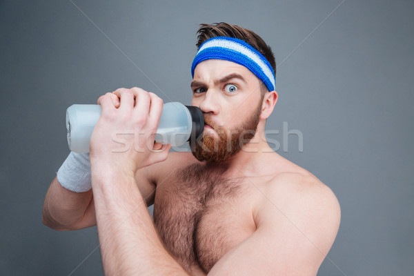 Suspicious shirtless sportsman drinking water and looking at camera Stock photo © deandrobot