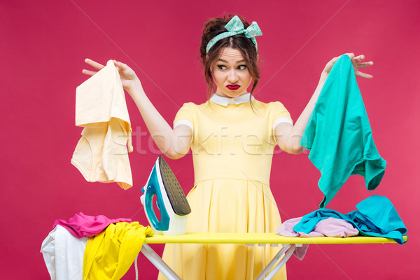 Unhappy irritated young woman holding and ironing clothes Stock photo © deandrobot
