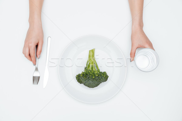 Hands of young woman drinking water and eating broccoli Stock photo © deandrobot