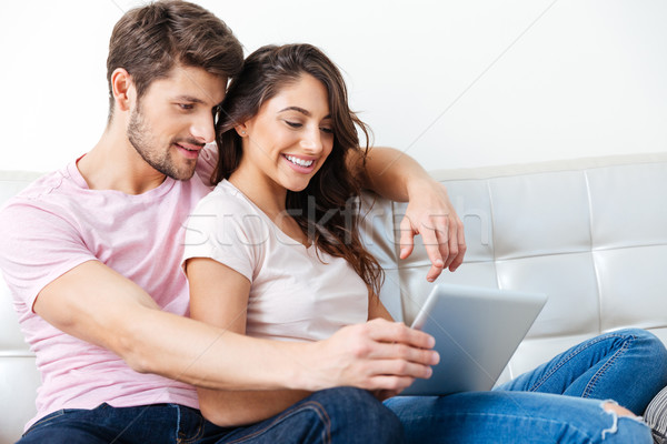 Smiling couple using pc tablet over white background Stock photo © deandrobot