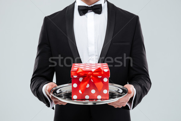 Closeup of butler in tuxedo holding tray with gift box Stock photo © deandrobot
