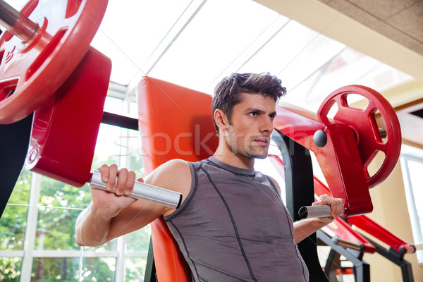 Portrait of a bodybuilder workout on fitness machine at gym Stock photo © deandrobot