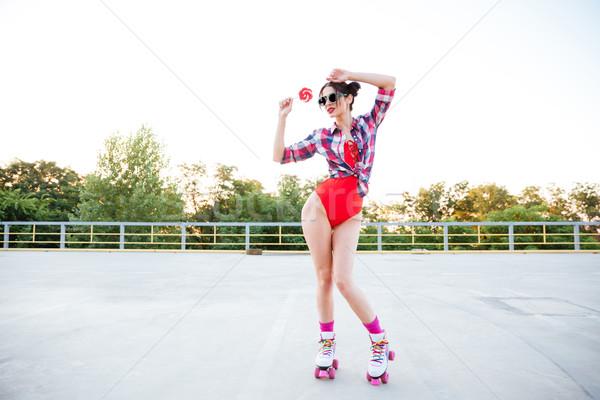 Belo mulher jovem pirulito em pé patins Foto stock © deandrobot