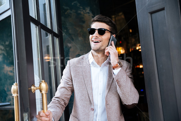 Businessman talking on cell phone and walking out from cafe Stock photo © deandrobot