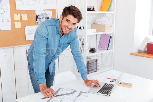 Smiling happy businessman standing at the office table Stock photo © deandrobot