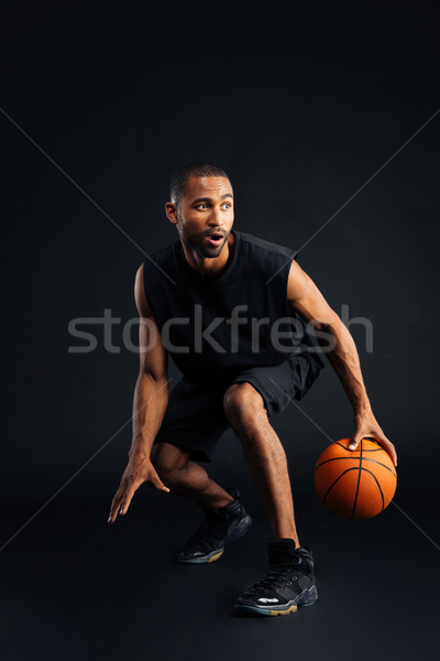 Portrait of a focused african sports man playing in basketball Stock photo © deandrobot