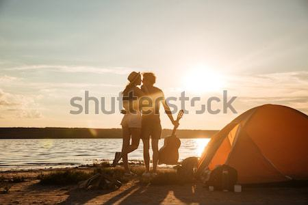 Silhouette of couple sitting near touristic tent and hugging Stock photo © deandrobot