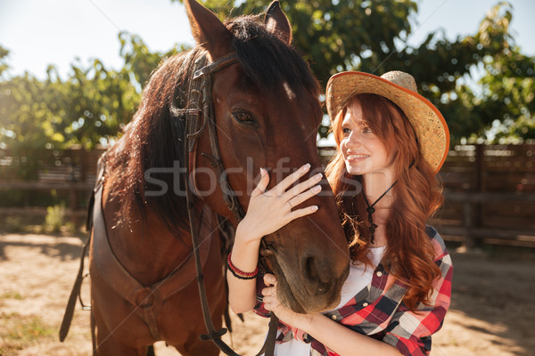 Young cowgirl taking care and hugging her horse at ranch Stock photo © deandrobot