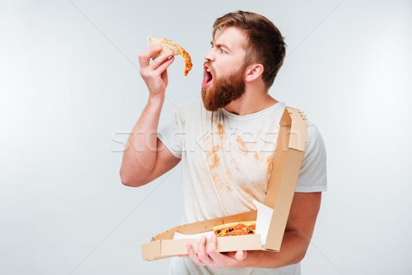 飢えた 男 食べ スライス ピザ 孤立した ストックフォト © deandrobot