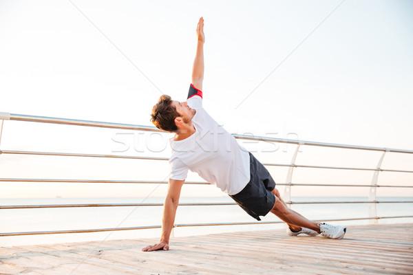 Fitness man doing yoga exercise outdoors Stock photo © deandrobot