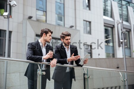 Two happy young businessmen with tablet standing and talking Stock photo © deandrobot