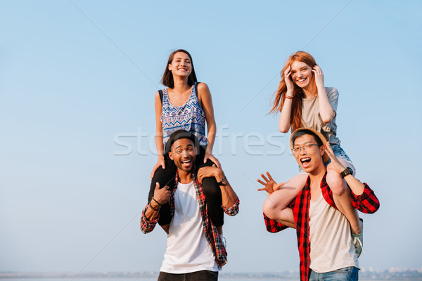Two cheerful women sitting on shoulders of their boyfriends Stock photo © deandrobot
