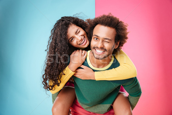 Portrait of happy african young couple having fun and winking Stock photo © deandrobot