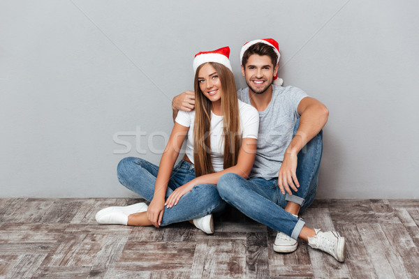 Happy couple in christmas hats are cuddling Stock photo © deandrobot