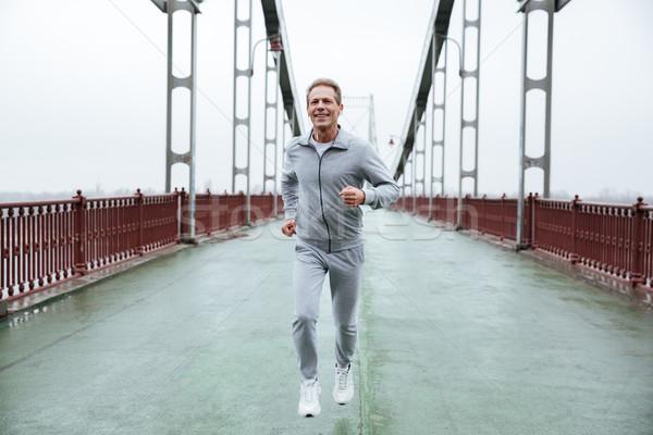 Full length Man running on bridge Stock photo © deandrobot