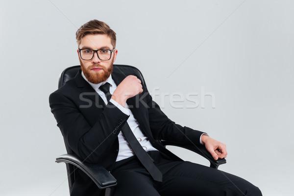 Człowiek biznesu okulary fotel brodaty czarny garnitur posiedzenia Zdjęcia stock © deandrobot