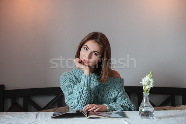 Pretty young lady sitting in cafe and reading magazine. Stock photo © deandrobot