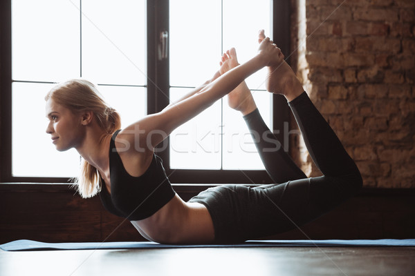 Beauitful young woman stretching and doing yoga exercises on mat Stock photo © deandrobot