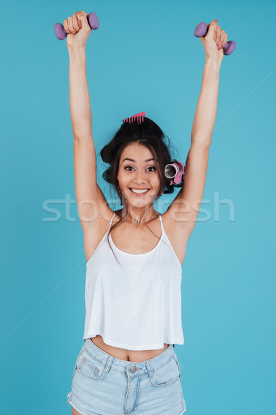 Happy young lady with hair curlers holding dumbbells Stock photo © deandrobot