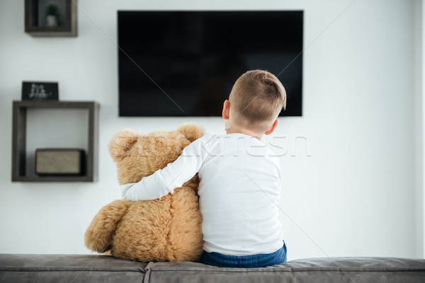 Back view image of cute little boy watching TV Stock photo © deandrobot