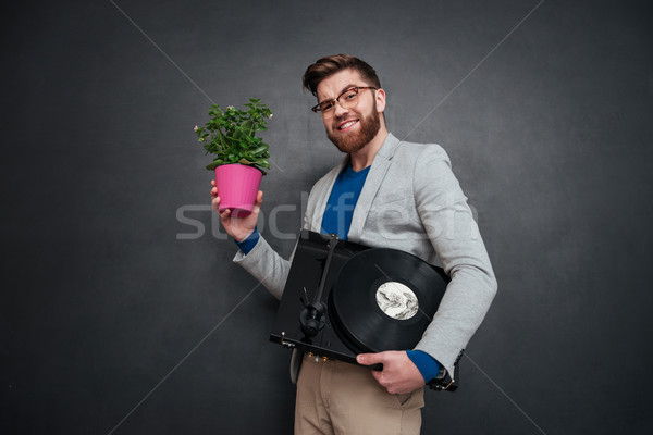 Cheerful bearded young businessman with flowers in pot and turntable Stock photo © deandrobot