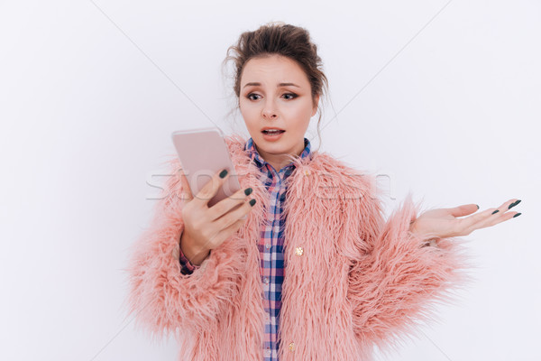 Surprised Woman in fur coat holding phone Stock photo © deandrobot
