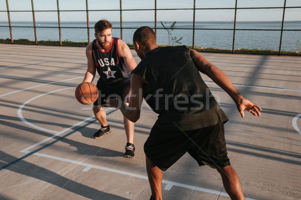 Two young sports men playing basketball at the playground Stock photo © deandrobot
