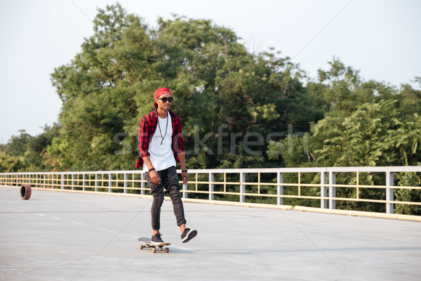 Young attractive dark skinned guy skateboarding Stock photo © deandrobot