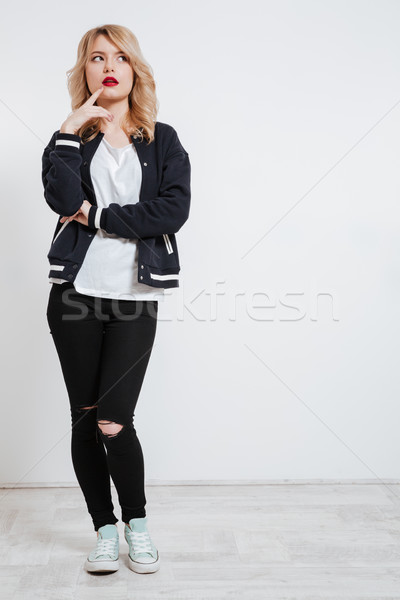 Pensive cute girl in casual clothes looking away Stock photo © deandrobot