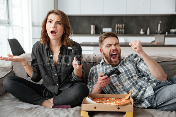 Couple playing games with console and eating pizza. Stock photo © deandrobot