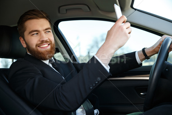 Vue de côté souriant homme d'affaires costume téléphone Photo stock © deandrobot