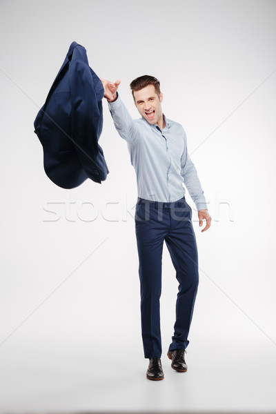Vertical image of man in business clothes throws jacket Stock photo © deandrobot